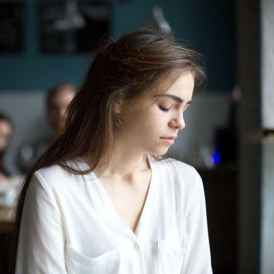 Ung kvinna ser sårad ut, i bakgrunden leende människor