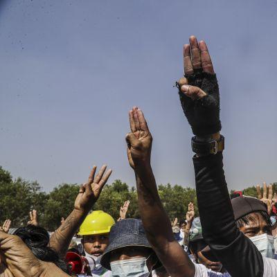 Tre finger hälsningen har blivit demokratiaktivisternas symbol i Myanmar. Bilden visar en grupp demonstranter vid begravningen av två ledande oppositionsaktivister i Rangoon.