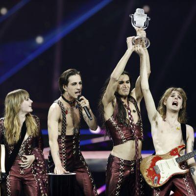 Ett band står på en scen och får en pokal. De är glada.
