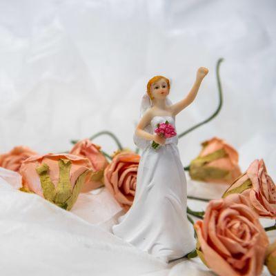 Brudpar i plast omgivet av blommor