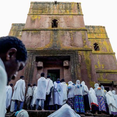 Pilgrimer samlas framför en klippkyrka i Lalibela.