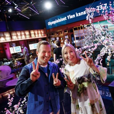 Mies ja nainen näyttävät voitonmerkkejä studiolavasteiden edessä