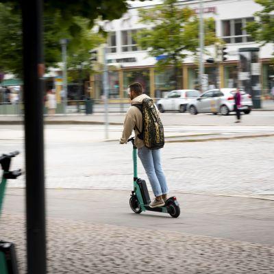 Mies ajaa sähköpotkulaudalla.