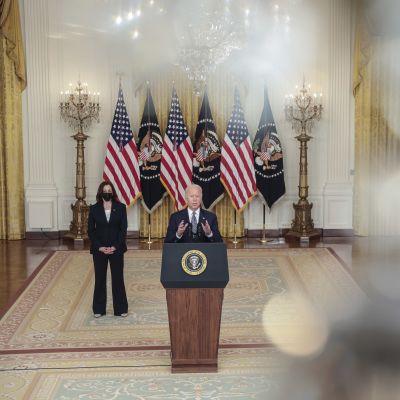 Mies seisoo puhumassa yleisölle, vierellä nainen maski kasvoillaan, taustalla Yhdysvaltojen lippuja.