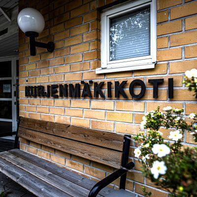 En gul tegelvägg med texten kurjenmäkikoti 2. Framför väggen finns en sliten bänk.