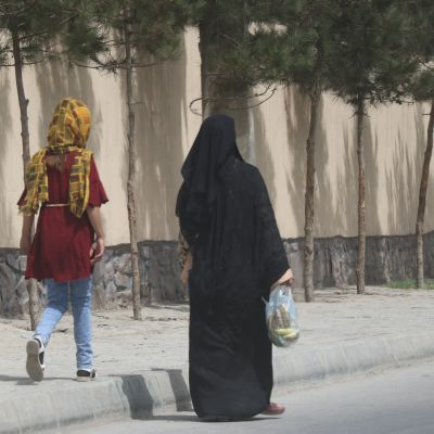En kvinna i burkha och en ung flicka i huvudduk som går på gatan i Kabul.