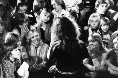 Anni-Frid från ABBA omringad av unga fans i Stockholm 1988. Hon har ryggen mot på bilden.