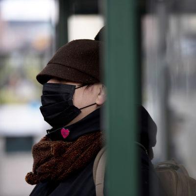 Hengityssuojaimeen pukeutunut bussipysäkillä.