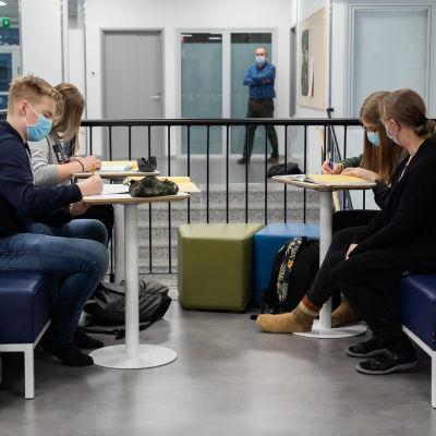 Opinto-ohjaaja Sari Heinonen seuraa, kun 9.-luokkalaiset Siiri Ylösmäki, Vilma Rautava ja Topias Kaapu tekevät matematiikan tehtäviä.
