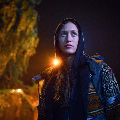nainen katsoo oikealle viistoon pimeässä, takana näkyy katuvalon loiste.
