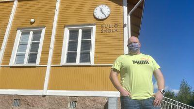 En man i gul t-skjorta står framför ett vitt trähus där det står Kullo skola.