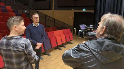 En man med filmkamera och en kvinna med mickrofon intervjuar en man i en konsersal.