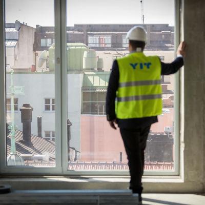 En man i hjälm och YIT-väst står vid ett fönster i ett nybyggt kontor.