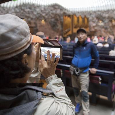 Japanilaisturistit kuvaavat toisiaan Temppeliaukion kirkossa.