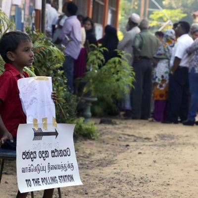 En pojke väntar på sina föräldrar, som röstar i Sri Lanka.