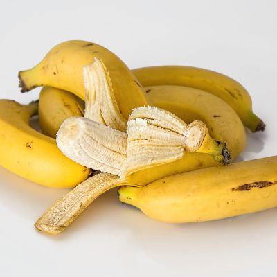 Kuvassa banaaneja, yksi kuorittu auki.