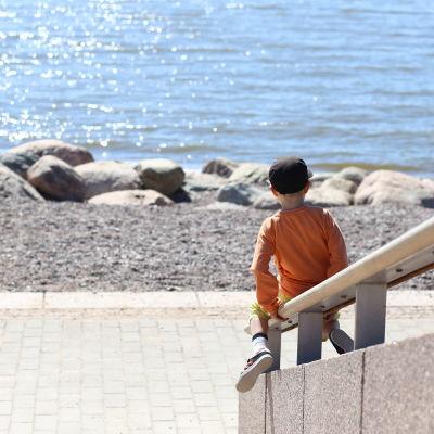 Lekande barn vid vattnet.