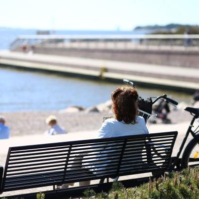 En kvinna sitter på en bänk framför vattnet.