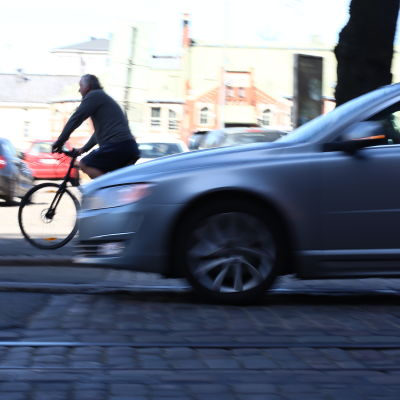 En bil kör nära en cyklist.