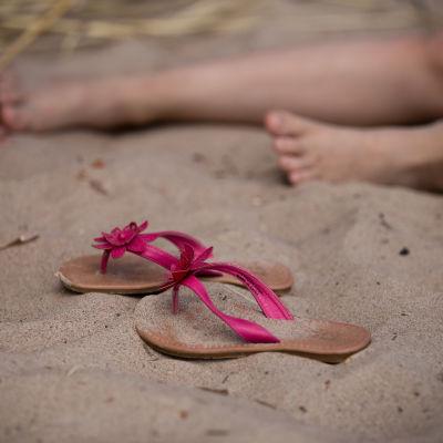 Pikkutytön sandaalit hiekkarannalla paljaiden varpaiden vieressä kesälomalla.