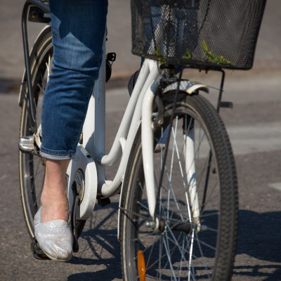 Anonyymi nainen pyöräilee kaupungissa kesällä.