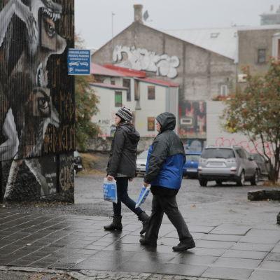 Kaksi ihmistä kävelee kadulla Reykjavikissa