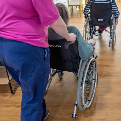Vårdare skuffar rullstol, i vilken en äldre person sitter.