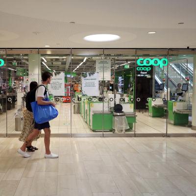 En man går förbi en stängd Coop butik.