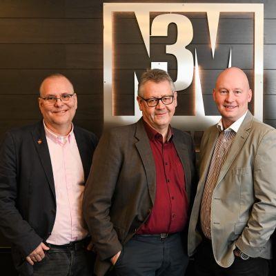 Fyra leende medelålders män står framför en företagsskylt där det står N3M. Fotat inomhus. Männen har skjorta och kavaj.