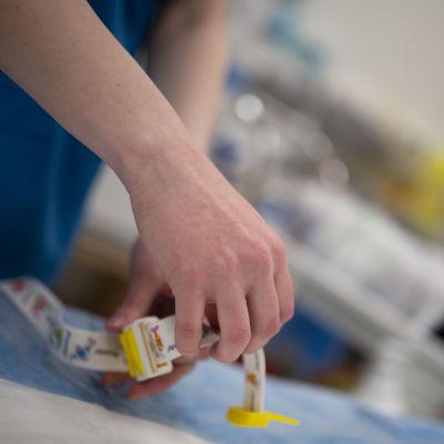 Hoitaja ottaa esille verenpaineenmittaukseen käytettävää hauskasti kuvioitua kiristysnauhaa Lastensairaalan ensiapuosastolla