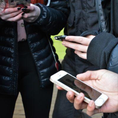 Kännyköitä nuorten käsissä välitunnilla.