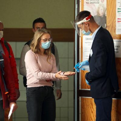 Äänestäjän käteen suihkutetaan käsidesiä.
