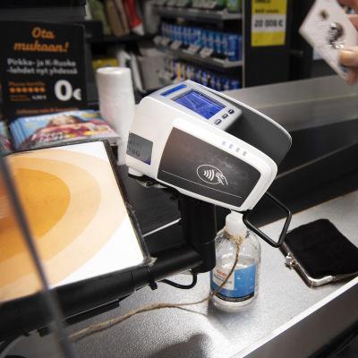 Asiakas maksaa pankkikortilla ruokakaupan kassalla.