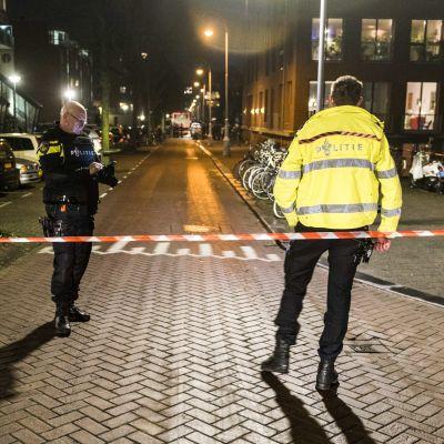 Två poliser står bakom avspärrat området efter skottdrama i Amsterdam.