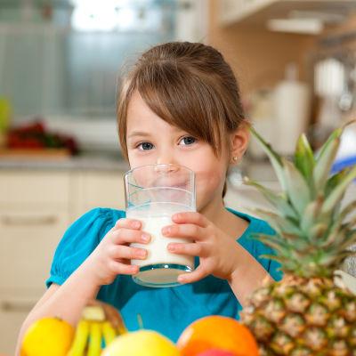 En flicka dricker ett glas mjölk.