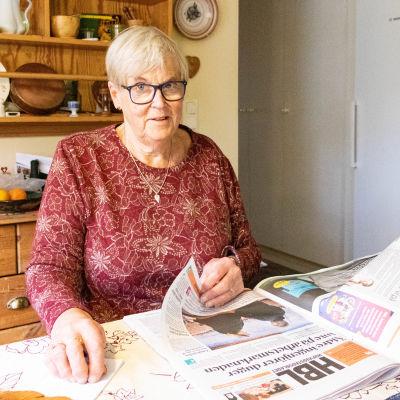 En kvinna som läser tidningen vid köksbordet.