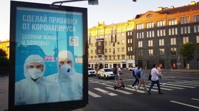 Moskvaborna uppmanas ta coronavaccin. En skylt i stadsbilden kommer med uppmaningen. I bakgrunden går folk över ett övergångsställe.