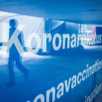 Koronarokotuspaikan lasiovesta heijastuu  ihmisen hahmo. Ikkunassa teksti, jossa lukee koronarokotus.