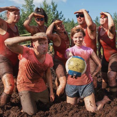 Ryhmä miehiä ja naisia pukeutuneina punaisiin uimapukuihin poseeraa rivissä, etualalla mies ja nainen pinkeissä paidoissa, nainen pitää lentopalloa. Koko joukko turpeen peitossa.
