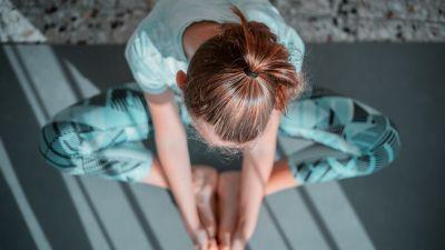 En kvinna i träningskläder sitter på en yogamatta och tänjer.