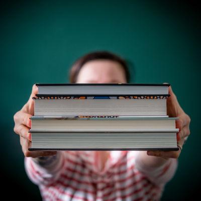 Person håller upp en packe böcker framför sitt ansikte.