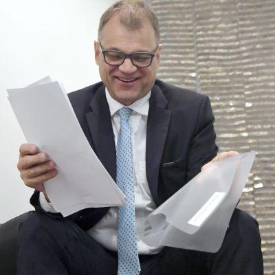 Centerns ordförande Juha Sipilä ser glad ut med en hög papper i famnen.