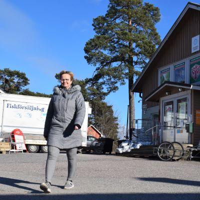 En kvinna i grå jacka går ute, i bakgrunden syns en liten bybutik och en fiskförsäljningsvagn.
