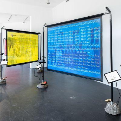Konstverk i galleri, med stora skärmar i gult och blått.