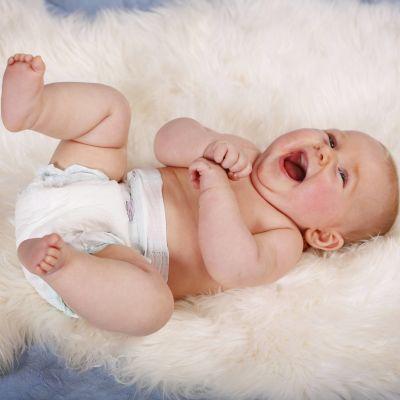 En bebis ligger på rygg på en filt och har på sig blöja.