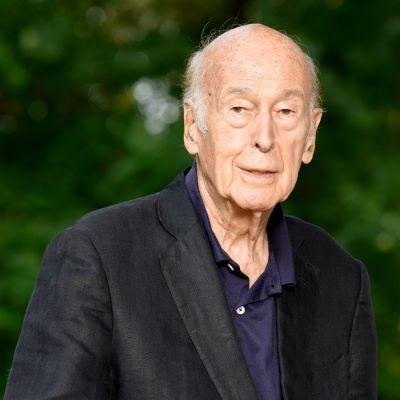En äldre kostymklädd man i halvnärbild mot en mörkgrön bakgrund. Frankrikes tidigare president Valéry Giscard d'Estaing fotograferad den 22 augusti 2018.