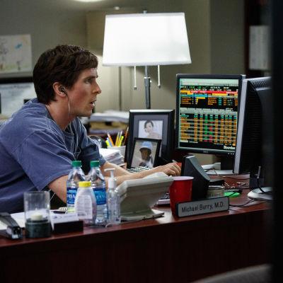Christian Bale sitter vid datorskärmar och undersöker börskurserna.