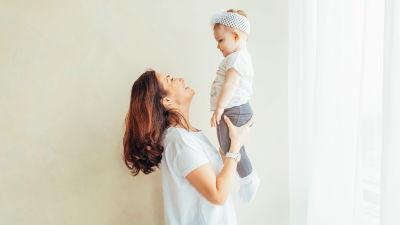 En mamma lyfter upp sitt barn i luften.