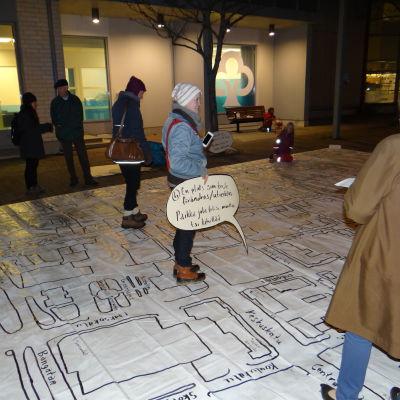 Kvinna står på en karta med en skylt i handen.