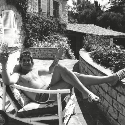 Svartvitt foto på Ozzy Osbourne i solstol med drink i trädgården